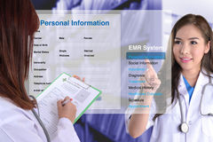The changing of medical record technology. Female doctor show how to use electronic medical record while another one checking patient information by hand Royalty Free Stock Photography