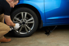 Changing modern car wheel. Man fixing car wheel Royalty Free Stock Photos