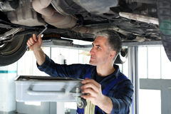 Changing the oil in the car services. Car mechanic lists the engine oil in the car services Royalty Free Stock Photos