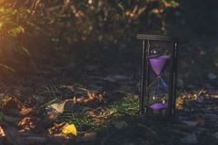 Changing seasons. Transience of life. Old hourglass on earth. Time passes quickly. Nature wakes up royalty free stock image