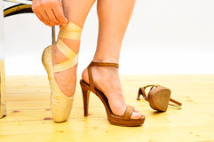 Changing shoes. Ballerina changing street shoes with ballet shoes Royalty Free Stock Photography