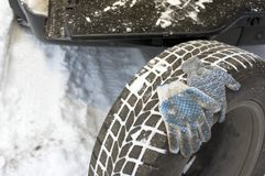 Changing a spare tire in winter. Changing a spare tire on the road, winter scene royalty free stock images