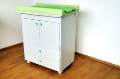 Changing table. Diapers changing table on hardwood floor Stock Photo