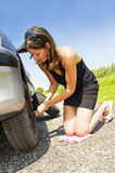 Changing a tire. Young woman kneeling, changing the front tire of her car Stock Photography