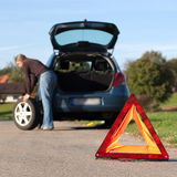 Changing the tire on a broken down car. On a road with red warning triangle Royalty Free Stock Photography