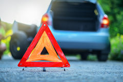 Changing tire on broken down car on a road with red warning triangle Stock Photo