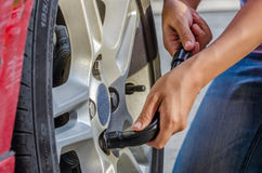 Changing tire with wheel wrench. Woman is changing tire with wheel wrench Royalty Free Stock Photography
