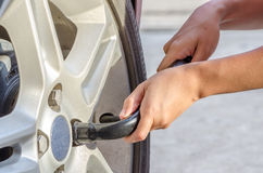 Changing tire with wheel wrench. Woman is changing tire with wheel wrench Stock Photography