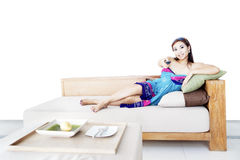 Changing TV channels. Young woman changing TV channels with remote control sitting on sofa at home Stock Image