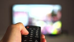 Changing TV channels by remote. Focus on hand and remote stock video