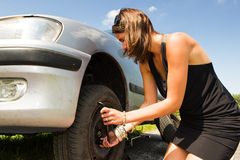 Changing a tyre. Young woman changing a flat tire on her car stock photo