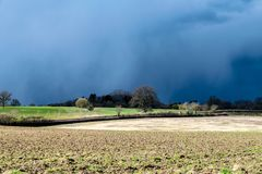 Dark clouds, storms and sunshine with changeable UK weather in early spring stock image