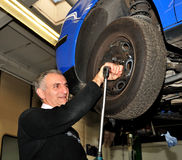 Changing a wheel. Man changing a wheel in a workshop Royalty Free Stock Photos