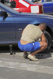 Changing the wheel. Man changing the car wheel in an automobiles parking Royalty Free Stock Photos
