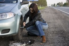 Changing the wheel. Woman trying to change the wheel Royalty Free Stock Image