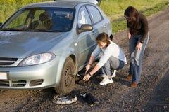 Changing the wheel. Man helping woman to change broken wheel Stock Image