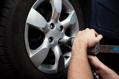 Changing wheel on car. Auto mechanic changing wheel on car with pneumatic wrench royalty free stock photos
