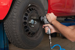 Changing the wheel with an impact wrench Royalty Free Stock Photos