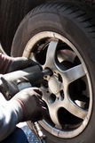 Changing the wheels in the automobile repair shop. Removing the wheel of a car in the automobile repair shop Stock Images
