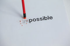 Changing the word impossible to possible with a pencil eraser Royalty Free Stock Image