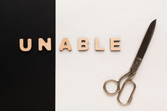 Changing word unable into able with scissors Royalty Free Stock Images