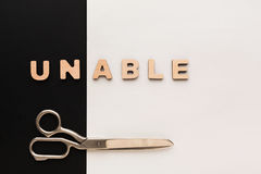 Changing word unable into able with scissors Stock Image