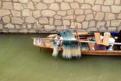 Changsha china: fishing boat under the bridge. In August 3rd 2013, Changsha, Hunan Xiangjiang, a fishing boat under the bridge; fisherman arranging nets Stock Images