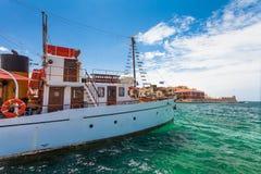 Chania, Крит - 26-ое июня 2016: Старый корабль для ежедневных круизов на обваловке старый городок Chania и маяка, Крита Стоковое Изображение RF