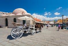 Chania, Creta - 26 de junho de 2016: O transporte do cavalo com cavalo branco, a mesquita dos Janissaries e os turistas estão na  Imagens de Stock