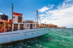 Chania, Crete - June 26, 2016: The old ship for daily cruises on the embankment the Old Town of Chania and Lighthouse, Crete Royalty Free Stock Image
