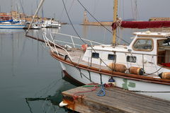 CHANIA, CRETE - MAY 29, 2014: The Venetian Outer Harbor with a sailing boat in the foreground Stock Photo