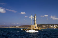 Chania lighthouse with sailboat Stock Images