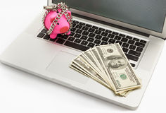 Chanined piggy bank and dollar on laptop Royalty Free Stock Image