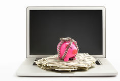 Chanined piggy bank and dollar on laptop Stock Image
