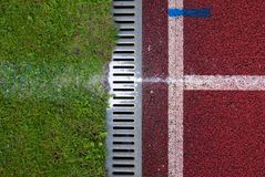 Channel at red running racetrack on the athletic stadium. Drain Stock Images