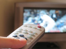 Channel Surfing. Close-up of TV remote control with sport on TV in the background royalty free stock image
