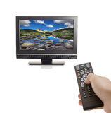 Channel surfing. A hand holding a remote control and a LCD TV against white background Stock Photos