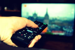 Channel surfing on television. A photo of a remote and hand with a television Stock Photography