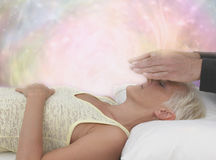 Channeling Healing Energy. Female patient lying with eyes closed and male healer with hands hovering above her face, channeling energy to her third eye, with royalty free stock image