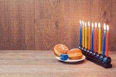 Chanoeka menorah met kleurrijke kaarsen en sufganioyt over houten achtergrond Royalty-vrije Stock Fotografie