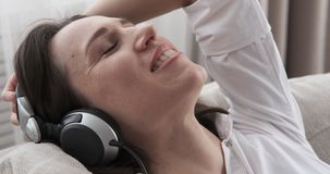 Chanson chanteuse et de écoute de femme décontractée dans des écouteurs clips vidéos
