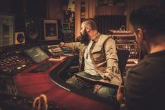 Chanson d'enregistrement d'ingénieur du son et de guitariste dans le studio d'enregistrement de boutique Photo stock