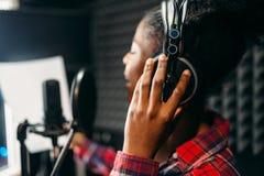 Chansons de jeune femme dans le studio d'enregistrement audio photo stock