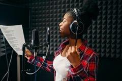 Chansons de jeune femme dans le studio d'enregistrement audio image libre de droits