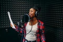 Chansons de jeune femme dans le studio d'enregistrement audio images stock