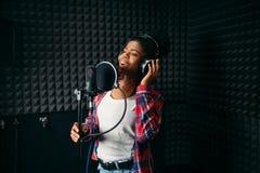 Chansons femelles d'interprète dans le studio d'enregistrement audio photographie stock