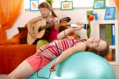 Chant de jeune fille, posant sur la bille de gymnastique Images stock