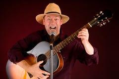 Chantant et jouant la guitare acoustique Images libres de droits