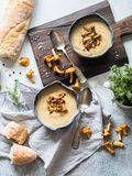 Chanterelle cream soup in blue bowls and baguette on the rustic table and wood board. Autumn food concept. Top view royalty free stock photography