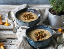 Chanterelle cream soup in blue bowls and fresh thyme in metal cup stock photography